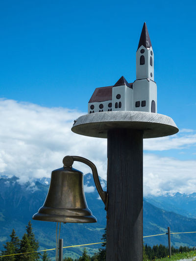 OLYMPUS DIGITAL CAMERA Heidiland Church Switzerland Graubünden Pizol Sky Cloud - Sky Nature Blue Day No People Mountain Outdoors Low Angle View Sunlight Birdhouse Religion Cross Land Belief Metal Architecture Wood - Material Focus On Foreground Wooden Post