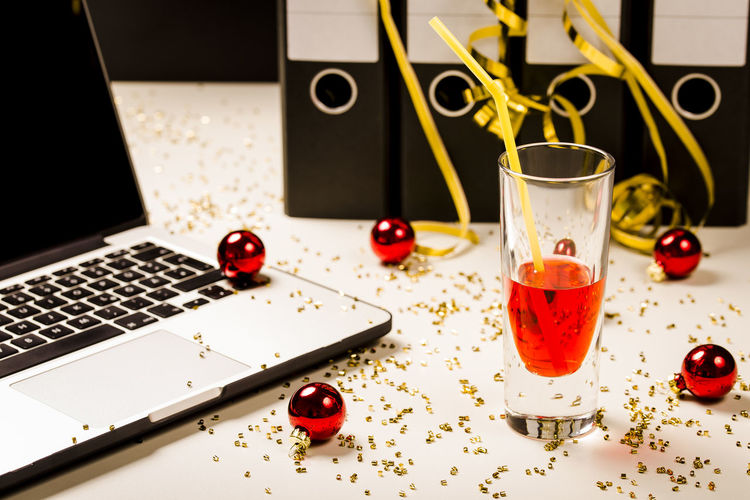 Laptop by drink glass on table during christmas