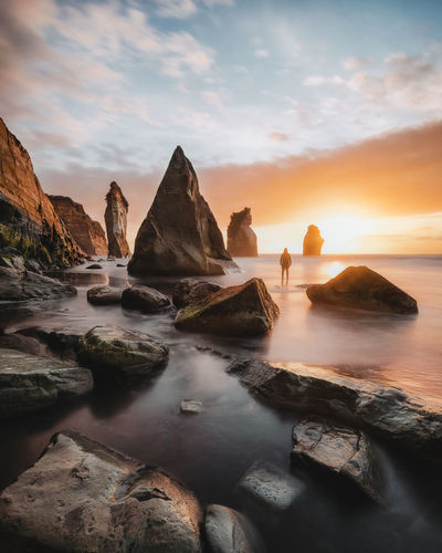 Scenic view of rocks in sea against sky during sunset