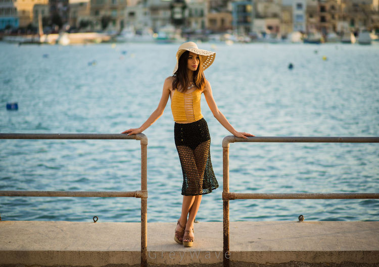 Full length of woman standing by railing against sea