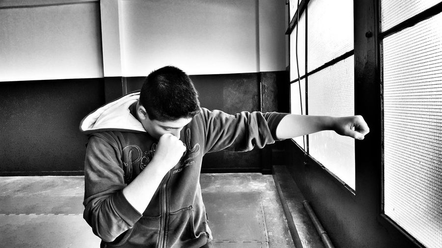 Boy punching by window in room
