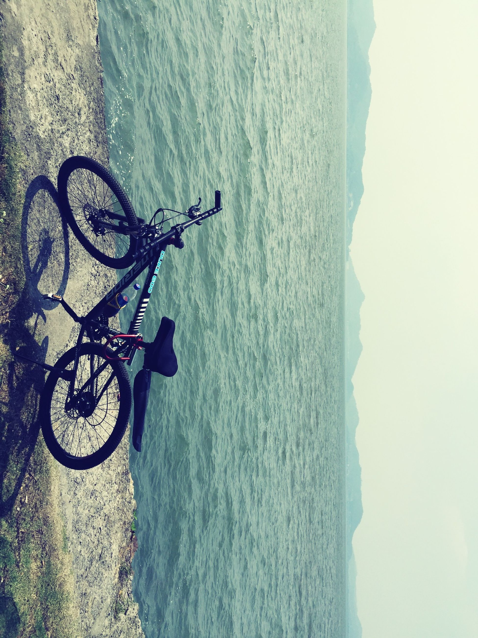 bicycle, transportation, mode of transport, land vehicle, sky, tranquility, nature, scenics, stationary, tranquil scene, riding, beauty in nature, parking, day, travel, mountain, water, sunlight, parked