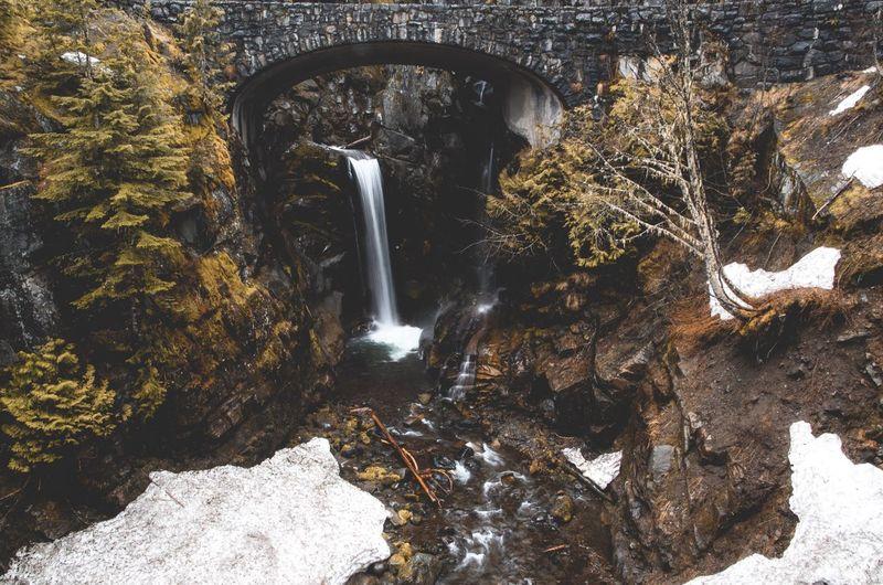 Waterfall at mount rainier seen through arch bridge