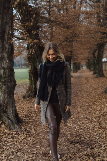 Smiling young woman walking during autumn