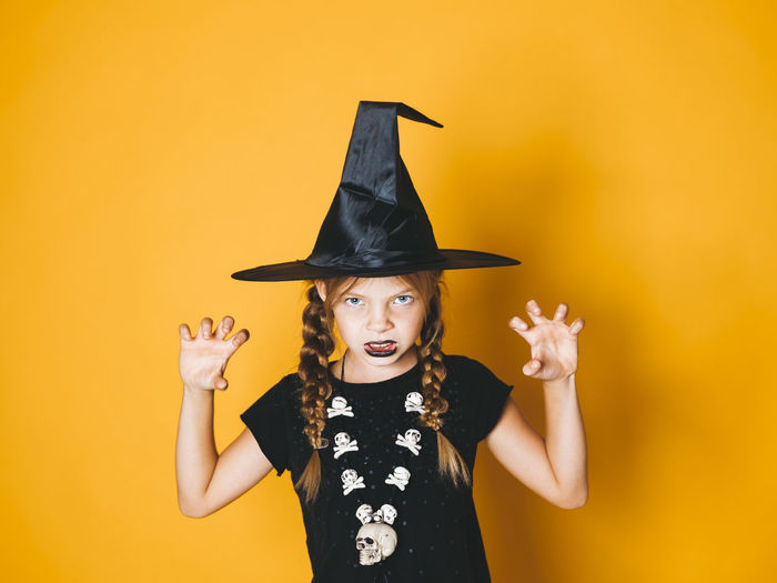 young halloween witch on orange background with black hat Halloween Halloween EyeEm Halloween Horrors Halloween_Collection Arms Raised Black Color Celebration Colored Background Costume Front View Gesturing Girl Halloween Human Arm Indoors  Looking At Camera Mouth Open One Person Portrait Standing Studio Shot Waist Up Witch Women Yellow Yellow Background