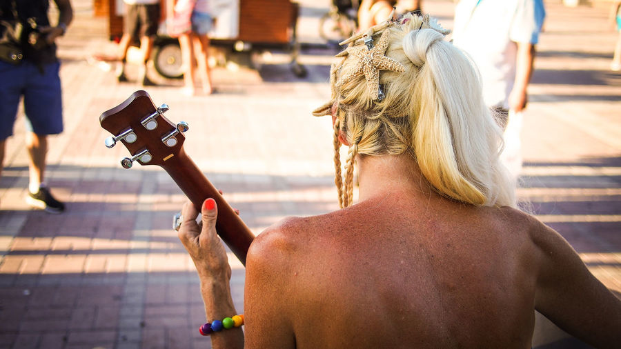 Rear View Of Shirtless Woman Playing Guitar On Street