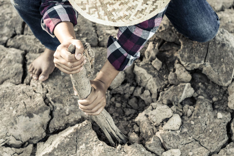 Low Section Of Woman Digging Barren Land
