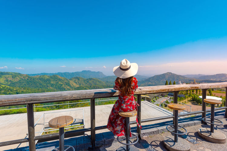 Woman standing on railing against mountain and blue sky