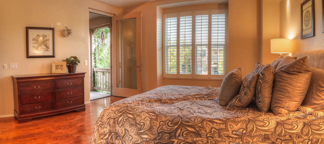 Large master bedroom with recessed lighting, wood floors and feng shui decor. The bed has a tan pattern duvet comforter with fluffy pillows Bay Window Bedroom Decor Design Duvet Hardwood Floor Home House Interior Interior Design Lamp Pillows Relaxing Rest Style
