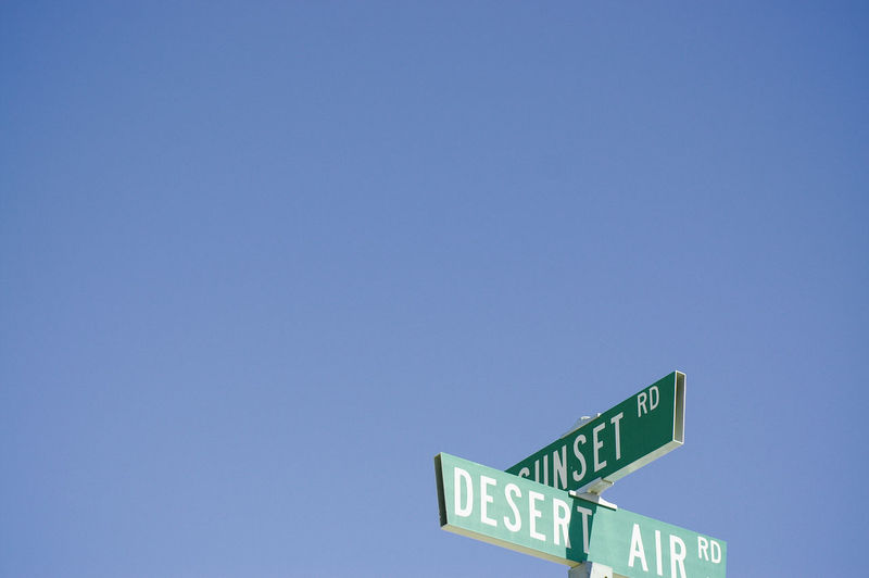 Low Angle View Of Road Sign Against Clear Blue Sky