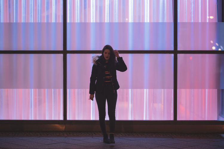Full length portrait of woman standing against illuminated wall