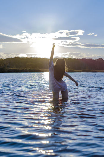 Arms Raised Beauty In Nature Cloud - Sky Day Human Arm Lake Leisure Activity Lifestyles Nature One Person Outdoors Real People Rear View Scenics - Nature Sky Sunlight Tranquil Scene Tranquility Water Waterfront Women