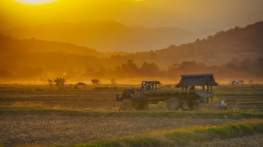 Scenic view of farm against mountains during sunset