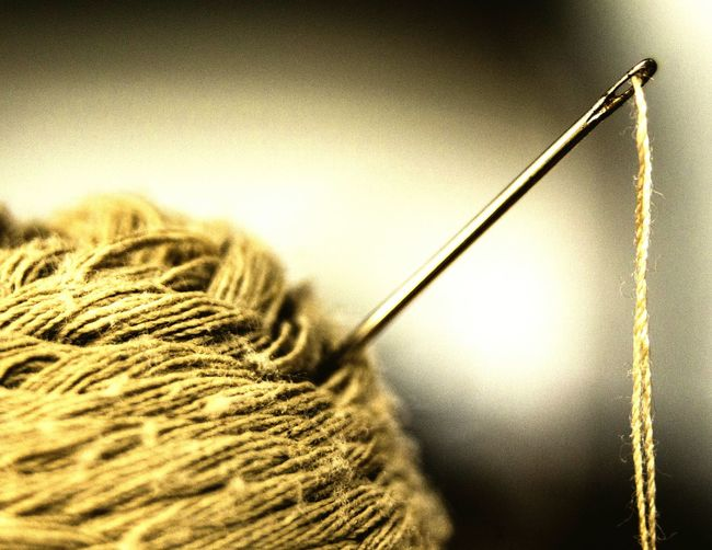Close-up of sewing needle in wool