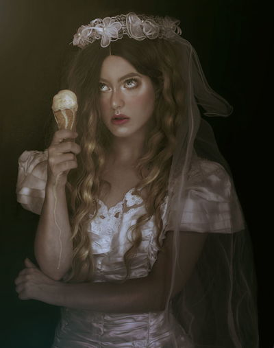 Thoughtful female model in costume having ice cream cone against black background