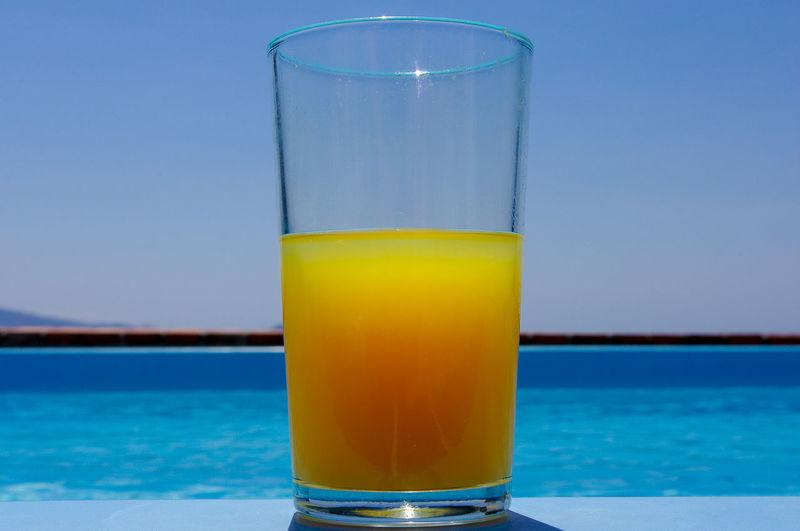 Close-up of orange juice on table against sea