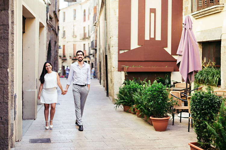 Portrait Of Happy Couple Holding Hands And Walking On City Street