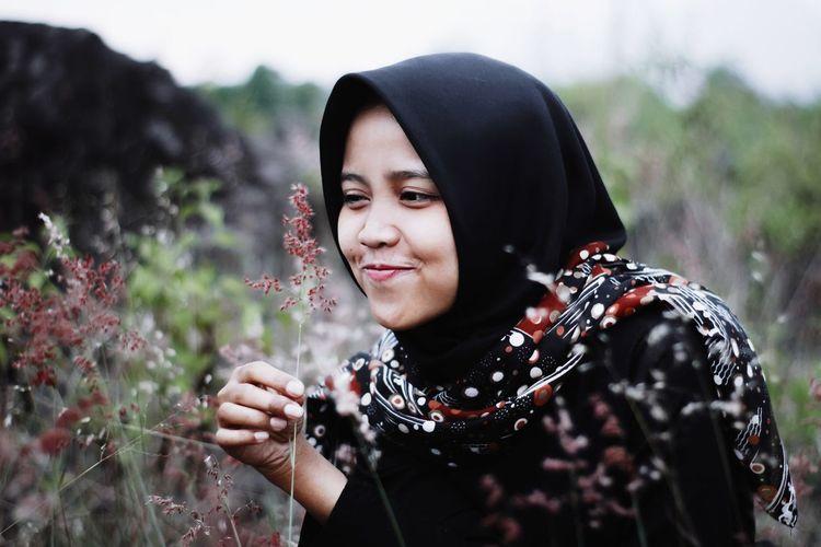 Close-up of smiling woman wearing hijab looking at plant