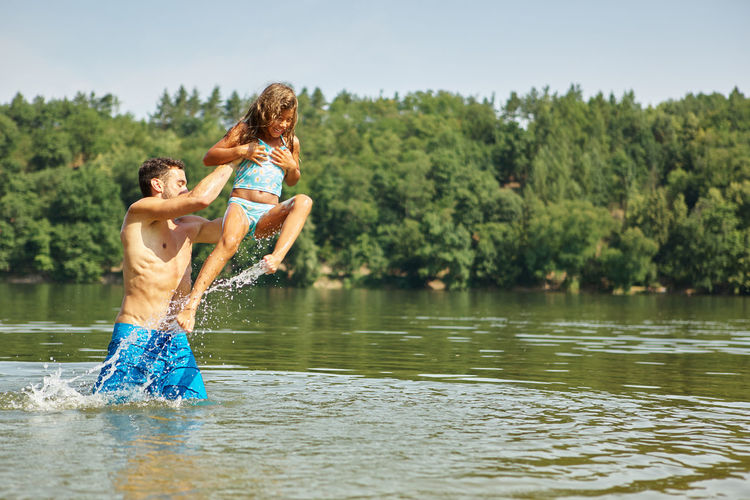 people enjoying in lake against trees Active Activity Adult Bathing Carefree Cheerful Child Clothing Cooling  Couple - Relationship Daughter Emotion Family Family Holidays Father Fun Girl Holiday Lake Leisure Leisure Activity Lifestyle Lifestyles Males  Man Men Nature Nonsense Outdoors Outside People Play Positive Emotion Real People Refreshment Romp Roughhouse Shirtless Single Splashing Splatter Spray Summer Three Quarter Length Throw Together Togetherness Tree Two People Vacation Water Waterfront Wet Women Young