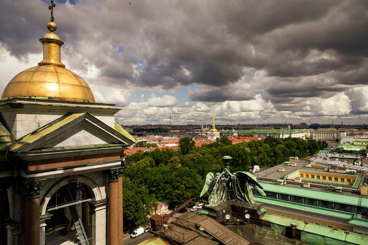 High angle view of cathedral and buildings against cloudy sky