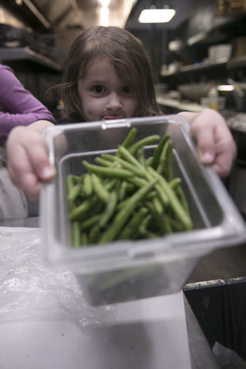 Girl Holding Green Beans In Container In Kitchen