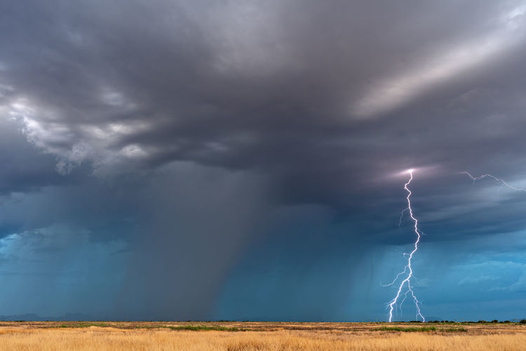 Lightning over field against storm clouds