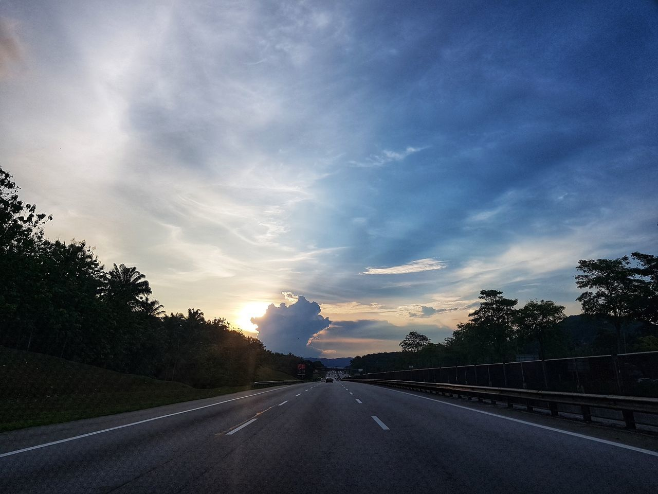 road, transportation, sky, cloud - sky, the way forward, direction, tree, symbol, nature, plant, sunset, diminishing perspective, road marking, mode of transportation, no people, marking, sign, beauty in nature, highway, motor vehicle, outdoors, dividing line, long