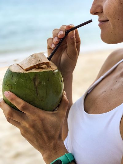 Midsection of woman drinking coconut water at beach