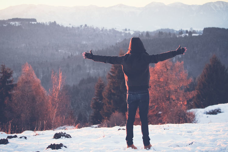 A man with arms raised standing on the snow in the mountain, looking at the horizon