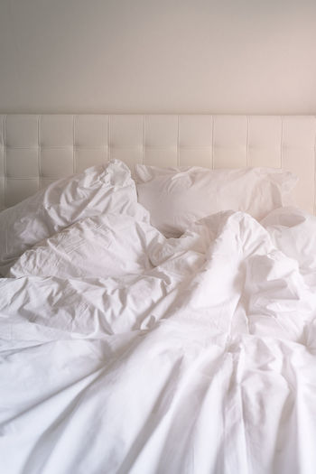 Close-Up Of White Pillows And Sheet On Bed