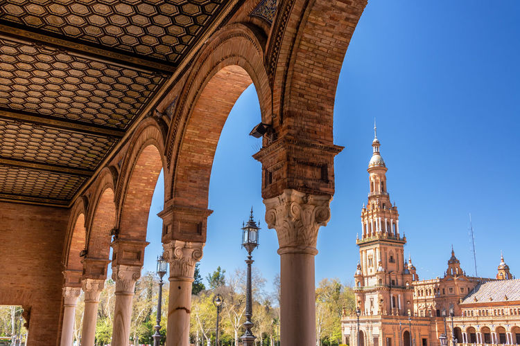 Arches in Plaza de Espana with a tower in the background in Seville, Spain Seville Sevilla Architecture Built Structure Building Exterior No People Europe SPAIN Travel Travel Destinations Tourism Façade Medieval European  Spanish Sky Plaza De España Arch Arches Architectural Column History Building Day