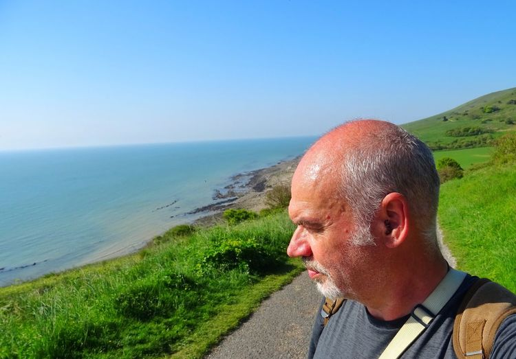 Mature Man Looking At Sea Against Clear Sky During Sunny Day