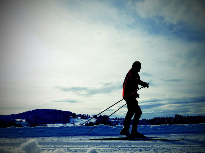 Full Length Of Man Skiing On Snow Covered Field Against Sky