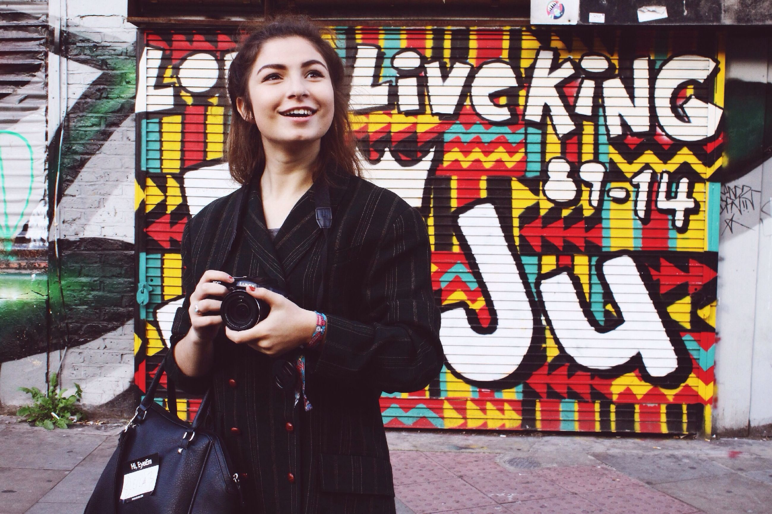 young adult, lifestyles, person, looking at camera, young women, front view, portrait, casual clothing, leisure activity, standing, happiness, smiling, three quarter length, wall - building feature, graffiti, full length, built structure