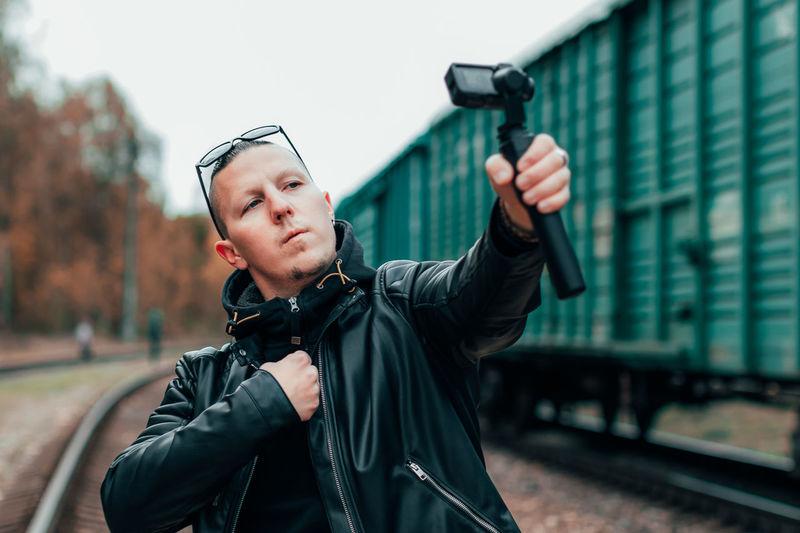 Portrait of man photographing through train