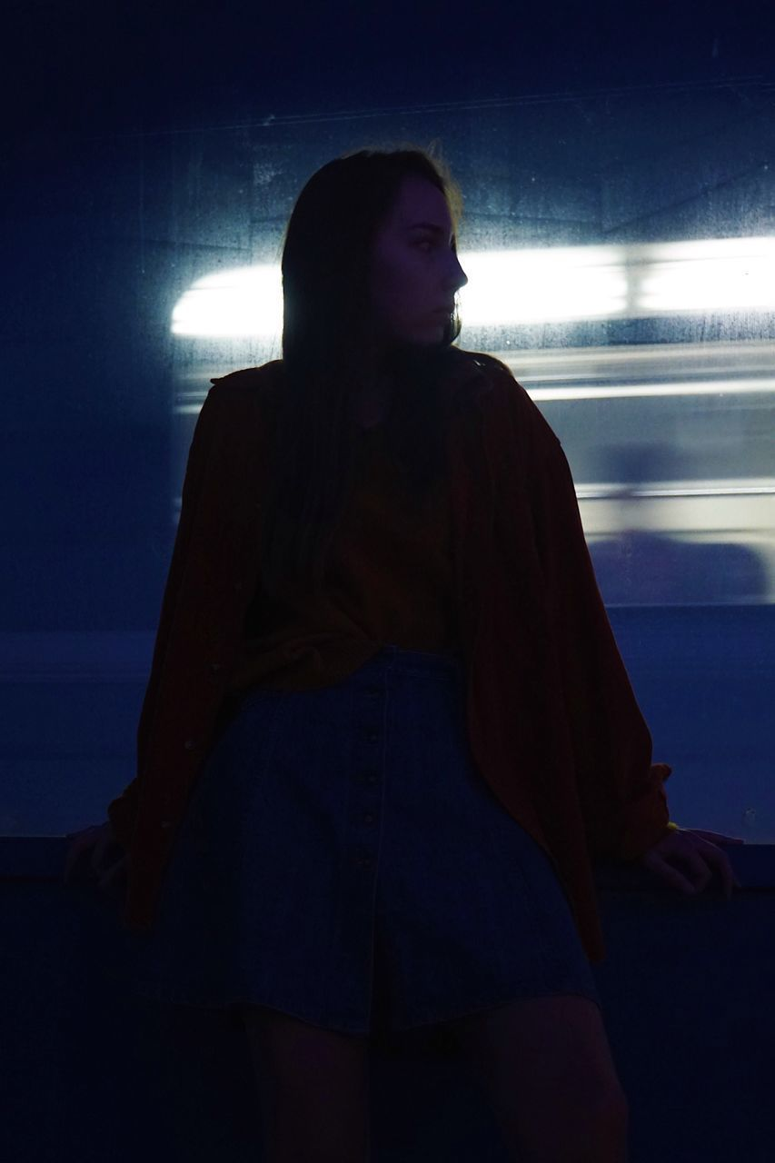 one person, real people, standing, lifestyles, night, leisure activity, three quarter length, front view, illuminated, young adult, casual clothing, long hair, looking, young women, hairstyle, looking away, women, indoors, hair, beautiful woman, contemplation, nightlife, teenager