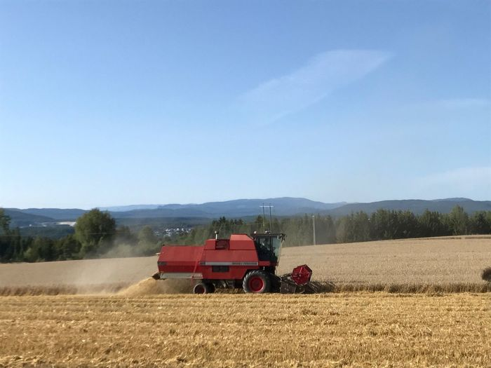 Field Agriculture Farm Rural Scene Combine Harvester Day Crop  Agricultural Machinery Landscape Nature Sky Mountain Outdoors No People Growth Scenics Beauty In Nature