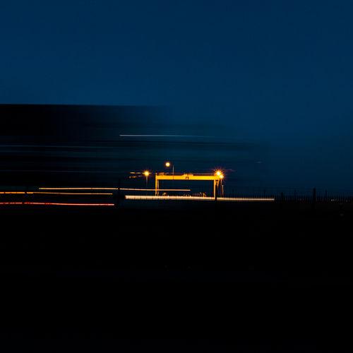 Illuminated light trails on street against sky at night