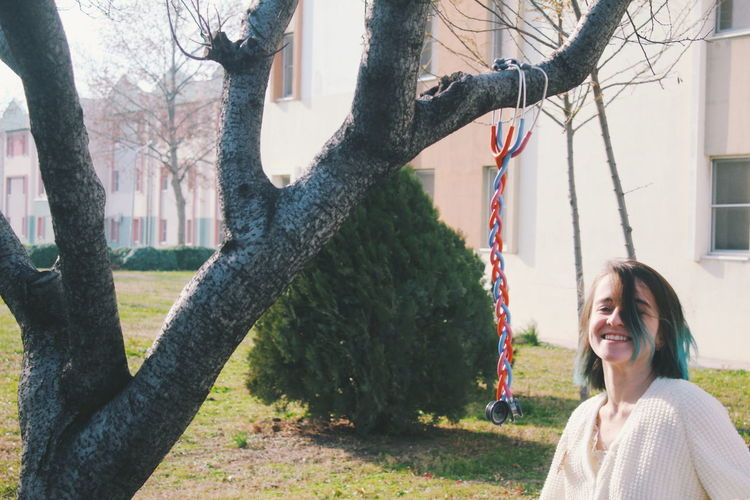Smiling Young Woman By Tree Trunk