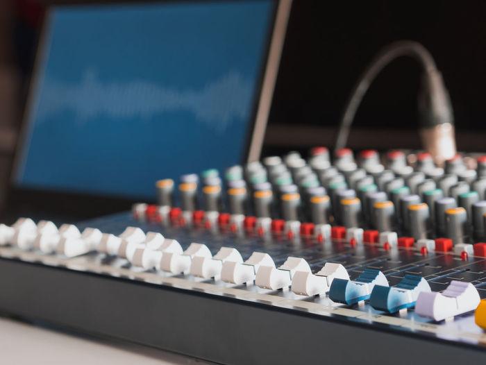 Close-up of sound mixer and laptop