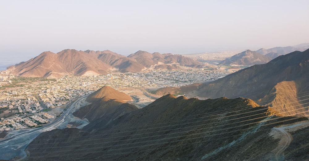 Scenic view of desert mountains against clear sky in khorfakan uae.
