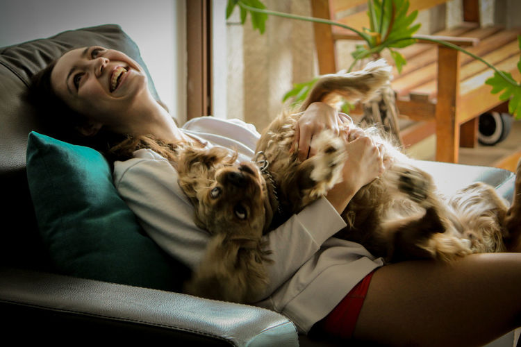 Rear view of woman with dog at home