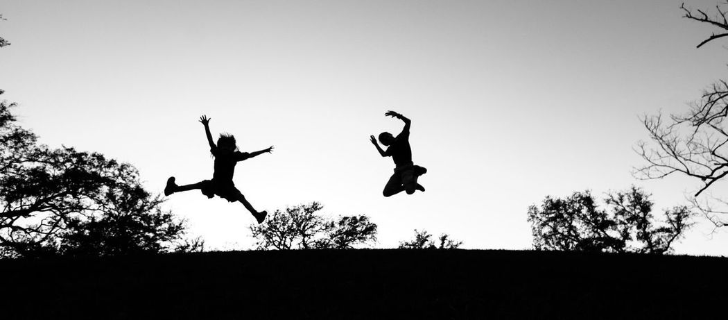 Silhouette of kids jumping at the park Blackandwhite Jump Playful Kids Mid-air Silhouette Jumping Low Angle View Tree Clear Sky Energetic Motion Outdoors People Real People