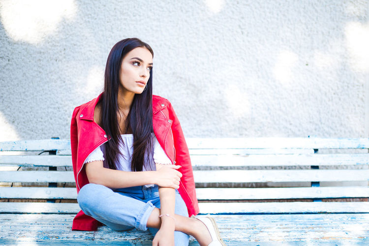 Beautiful Young Woman Sitting On Bench Against Wall