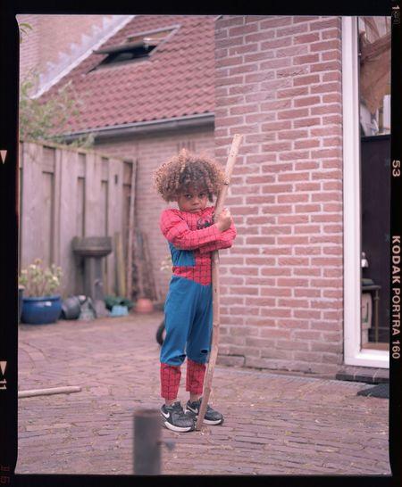 Girl standing outside house against building