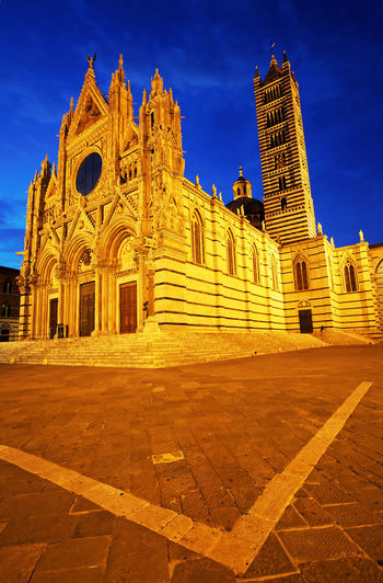 Low angle view of siena cathedral against blue sky at dusk