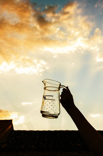 Low angle view of hand holding drink against sky during sunset