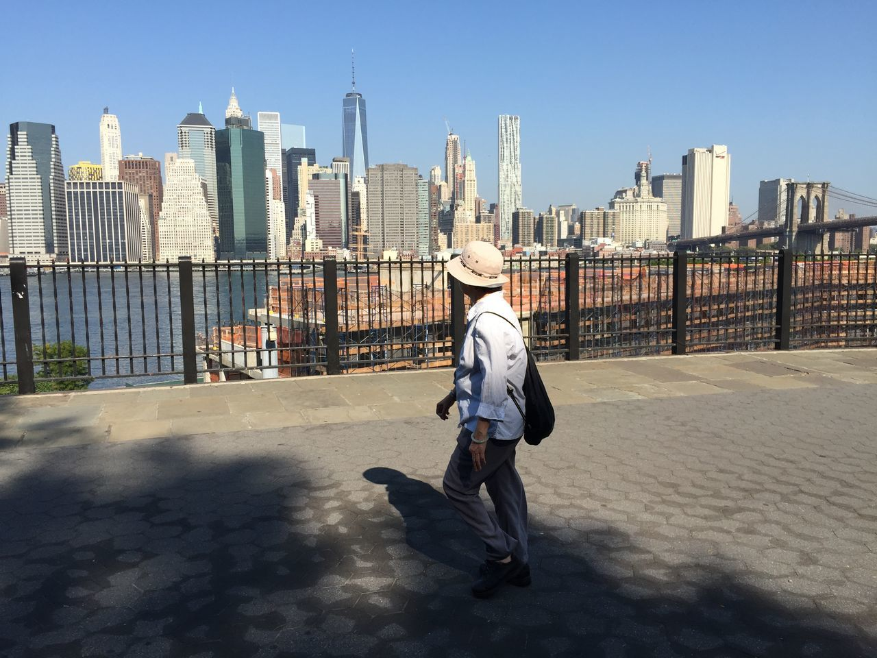 Full length of man walking on footpath by one world trade center and city against clear blue sky