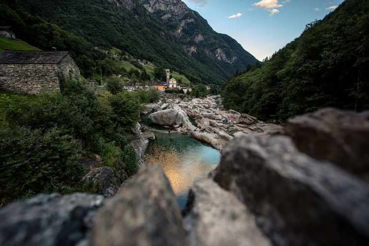 Stream by rocks against mountains