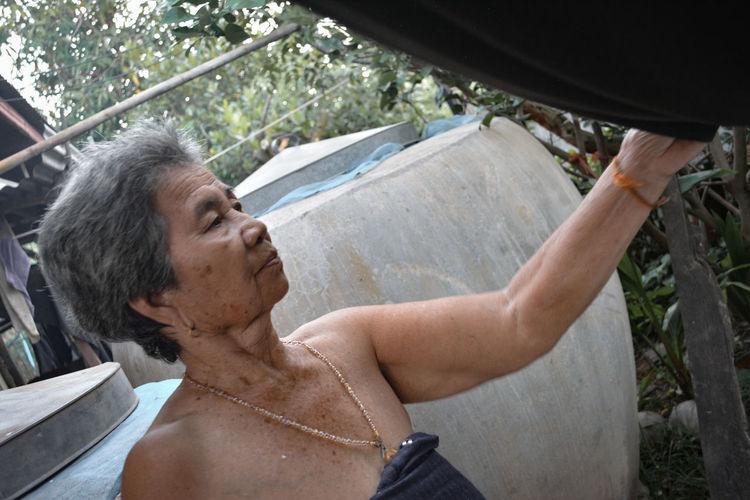 Portrait of shirtless man holding camera in yard
